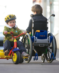 Image of child in wheelchair with Power Pack add-on