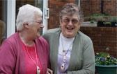two elderly women wearing alarm pendants
