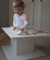 Image of child standing in box table support