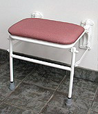 Image of padded wall-mounted shower seat from Pressalit Care