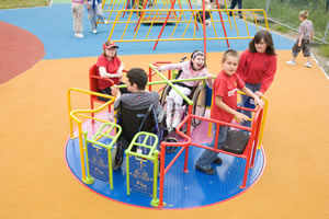 children playing on Ability Whirl roundabout