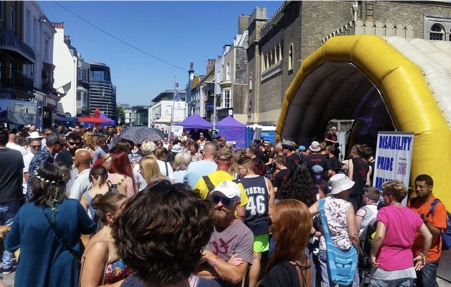 Image of last year's festival with crowds of participants and showing the staging area where performers played throughout the day